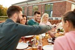 Freunde, die Burger am Abendessen auf Dachspitze essen stockbild