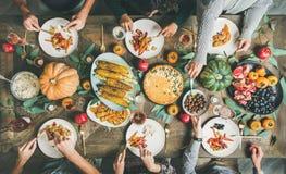 Freunde, die am Danksagungs-Tagestisch mit vegetarischen Mahlzeiten essen lizenzfreies stockfoto