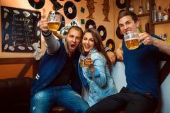Freunde, die das Spaßlächeln und -getränk an der Bar haben Stockfotografie