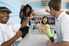 Freunde, die an der Bowlingbahn zujubeln Lizenzfreies Stockfoto