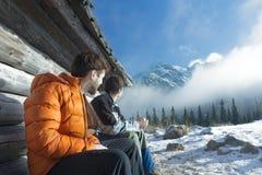 Freunde, die draußen auf hölzerner Bank in den Winterbergen stillstehen Lizenzfreie Stockfotos