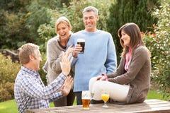 Freunde, die draußen Getränk im Pub-Garten genießen Stockbild