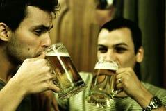 Freunde, die ein Bier zusammen essen Lizenzfreie Stockfotos