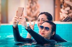 Freunde, die ein selfie auf dem Pool schwimmen und nehmen stockbild