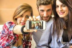 Freunde, die ein selfie mit Telefon nehmen stockbilder