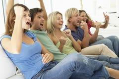 Freunde, die ein Spiel auf Fernsehen überwachen Stockbild