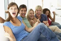 Freunde, die ein Spiel auf Fernsehen überwachen stockfotografie