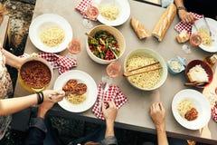 Freunde, die eine Mahlzeit von Spaghettis Bolognaise genießen lizenzfreies stockfoto