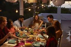 Freunde, die an einem Abendessen auf einem Patio, erhöhte Ansicht sprechen stockfotos