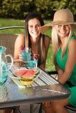 Freunde, die an einem lachenden und lächelnden Café zu Mittag essen Stockfotografie