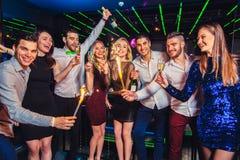 Freunde, die in einem Nachtklub partying und Getränke geröstet worden sein würden stockfotografie