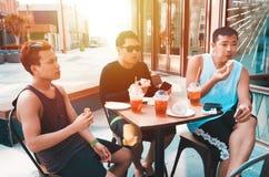 Freunde, die einen Imbiss essen stockbilder