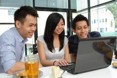 Freunde, die einen Laptop verwenden Lizenzfreie Stockfotos
