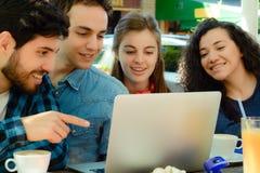 Freunde, die in einer Kaffeestube mit einem Laptop sich treffen lizenzfreie stockfotos