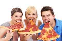 Freunde, die enorme Pizzascheiben essen stockbilder