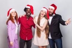 Freunde, die für das Feiern von Weihnachten sich treffen Tragende Sankt-Rotkappe Lizenzfreie Stockfotos