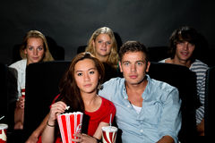 Freunde, die Film am Kino aufpassen Lizenzfreie Stockfotografie