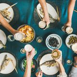 Freunde, die Fisch und essen und Bier, quadratische Ernte trinken lizenzfreie stockfotografie