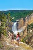 Freunde, die Fotos machen und schöne Ansicht des Wasserfalls auf dem Wandern von Reise in den Bergen genießen stockbild