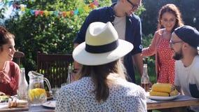 Freunde, die für Abendessen am Sommergarten zusammentreten stock video footage