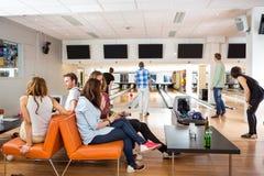 Freunde, die Freizeit im Bowlingspiel-Verein verbringen Stockfotografie