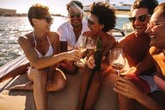 Freunde, die Getränke auf Yachtplattform haben lizenzfreie stockfotos