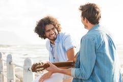 Freunde, die Gitarre spielen Stockbild