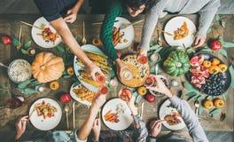 Freunde, die Gläser am Danksagungs-Tag mit vegetarischen Mahlzeiten klirren lizenzfreie stockfotografie