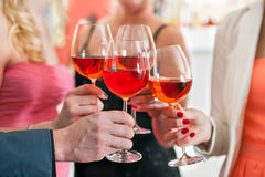 Freunde, die Gläser Rotwein werfen Stockfotos