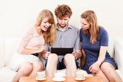 Freunde, die Graseninternet auf Tablette sich entspannen Stockfotografie