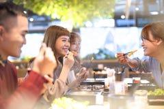 Freunde, die heißen Topf im Restaurant essen stockbild