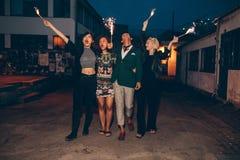 Freunde, die heraus mit Wunderkerzen auf Stadtstraße genießen Lizenzfreie Stockfotos