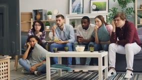 Freunde, die im Fernsehen traurigen Film, zusammen zu schreien aufpassen und Imbisse zu essen zu Hause stock video