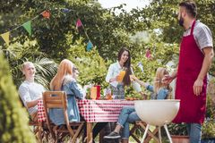 Freunde, die im Garten partying sind stockbilder