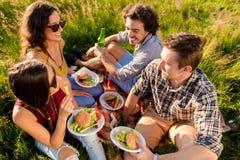Freunde, die im Gras sitzen und Burger an der Grillpartei essen stockfoto