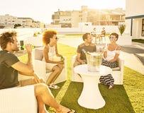 Freunde, die jede andere Firma in der Sonne mit Getränken genießen Lizenzfreies Stockfoto
