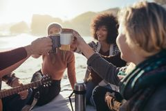 Freunde, die Kaffee am Strand zujubeln stockbild