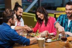 Freunde, die Lebensmittel am Restaurant essen und schmecken lizenzfreie stockbilder