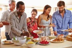 Freunde, die Lebensmittel sich dienen und am Abendessen sprechen Stockfotos