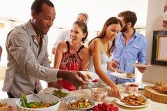 Freunde, die Lebensmittel sich dienen und am Abendessen sprechen Stockbild