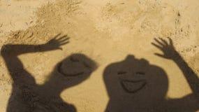 Freunde, die lustige Gesichter im Sand machen lizenzfreies stockfoto