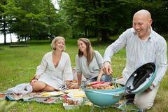 Freunde, die Mahlzeit an einem Picknick im Freien haben Lizenzfreie Stockfotos