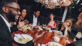 Freunde, die Mahlzeit im Restaurant heraus genießen kühlen stockbild