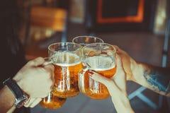 Freunde, die mit Gläsern hellem Bier an der Kneipe rösten Schöner Hintergrund der Gruppe Oktoberfest A der jungen Leute während r stockfotografie