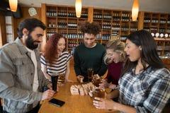 Freunde, die mit Holzklötzen beim Essen des Glases Bieres spielen Lizenzfreie Stockfotografie