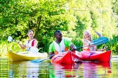 Freunde, die mit Kanu auf Fluss schaufeln Stockbilder