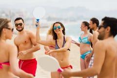 Freunde, die mit Schlägern am Strand spielen Stockbilder