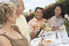 Freunde, die mit Wein bei Dinning feiern Stockfoto