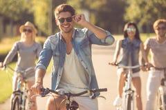 Freunde, die in Park radfahren lizenzfreie stockbilder