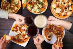 Freunde, die Pizza essen Draufsicht über die männlichen Hände, die Becher mit klirren stockbilder